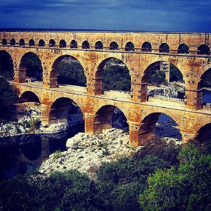 Pont du Gardin akvedukti Etelä-Ranskassa lähellä Nimesin kaupunkia. 50 kilometrin pituista kivistä rakennettua vesijohtoa pitkin virtasi 22 000 kuutiota vettä päivässä. Tarkkaan laskettu kallistus varmisti sen, että vesi virtasi omalla paineellaan. Akveduktin rakennuspiirrustuksia varten roomalaisten insinöörien oli mitattava tarkasti maaston korkeuserot. Vesi kulki matkallaan kohti kaupunkia tunnelien läpi ja siltoja pitkin joko kokonaan tai osittain katetussa kourussa. Roomalaisinsinöörit selvisivät vaativasta tehtävästään melko yksinkertaisilla apuvälineillä kuten luotilangalla.