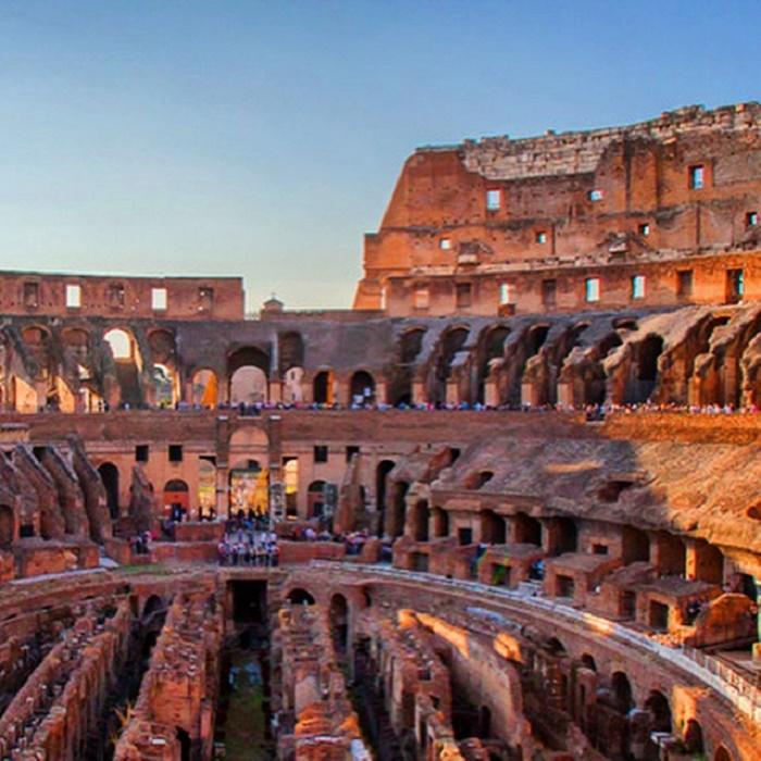 """Colosseum. Sen rakentamisen aloitti keisari Vespasianus 70-luvun alussa, ja se valmistui vuonna 80 Tituksen hallituskaudella. Antiikin aikana rakennus tunnettiin nimellä Amphitheatrum Flavium, """"Flaviusten amfiteatteri"""". Colosseum-nimitys otettiin käyttöön vasta keskiajalla. Nimi tulee joko rakennuksen suuresta koosta tai sen lähistöllä aikoinaan sijainneesta keisari Neron kolossaalisesta patsaasta."""