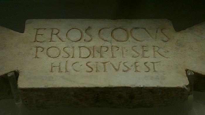 Muistokirjoitus kivilaatassa: Tässä lepää Eros, Posidippuksen kokki ja orja.