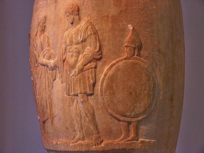 Parrakas orja kantaa isäntänsä kilpeä, 380-370 eKr. Ateenan arkeologinen museo.
