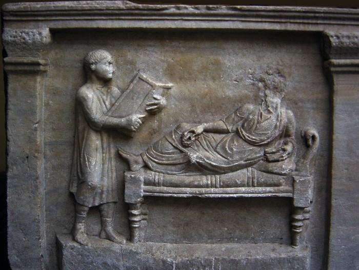 400-luvulta peräisin oleva reliefi Valerius Petronianuksesta ja hänen orjastaan, joka pitelee käsissään kirjoitustaulua.