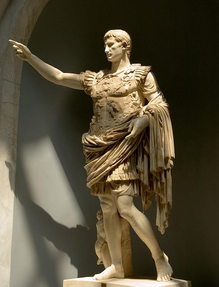 Tämä on luultavasti tunnetuin kuva keisari Augustuksesta. Tämä upea veistos on Vatikaanin museon kokoelmissa ja se tunnetaan nimellä Prima Portan Augustus. Veistos näyttää Augustuksen valloittajana, maailmanrauhan tuojana ja kultaisen aikakauden aloittajana. Keisari seisoo rauhallisena ja vaikuttavana hahmona, ja hänen jaloissaan on vauva, Eros, joka muistuttaa Augustusta hänen jumalallisesta alkuperästään. Veistoksen tehtävä on kertoa, että keisarin ansiosta valtiojärjestys on sopusoinnussa jumalten luoman maailmanjärjestyksen kanssa. Augustus on syntynyt maailmaan pitämään huolen siitä, että jumalten tahto ja oikeudenmukaisuus toteutuvat maailmassa. Hän varjelee ihmiskuntaa vääryydeltä lopetettuaan sodat ja luotuaan uuden hallitusjärjestelmän. Veistoksessa voimme myös nähdä kiteytettynä Augustuksen jälkimaineen kaikkein merkittävimpänä kaikista Rooman keisareista. Hänelle kuuluu kunnia siitä, että sisällissodat loppuivat ja Roomaan koitti rauhanaika. Valokuvaaja tuntematon.