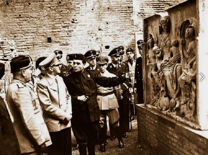 Benito Mussolini ja Adolf Hitler kuuntelevat oppaan selostusta fragmentista, joka esittää Saturnia Tellusta. Kuvassa näkyvät myös Joseph Goebbels, Heinrich Himmler ja Joachim von Ribbentrop. Kuva: Alinari Archives, Firenze.